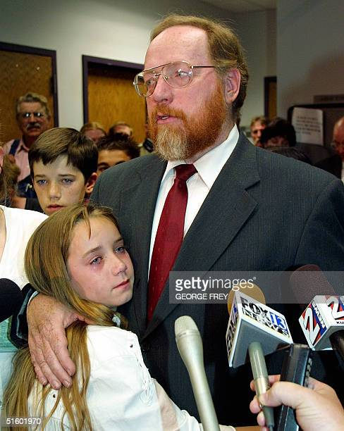 With tears rolling down her cheek Sierra Green holds on to her father Utah polygamist Tom Green as he talks to reporters after he was convicted on...