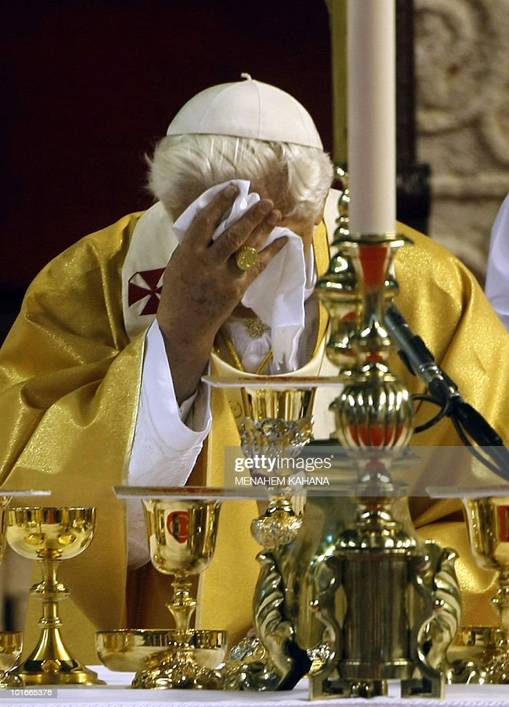 With temperatures in the mid-30 Celcius, Pope Benedict XVI dries his face as he leads a mass at the Eleftheria Sports Centre in Nicosia on June 6, 2010 on the third and final day of the pontiff's visit to the mostly Greek Orthodox Mediterranean island.