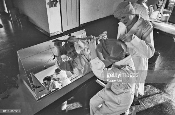 With the aid of a mirror, two female munitions workers tie their protective turban style head scarves prior to working a shift at a Royal Ordnance...