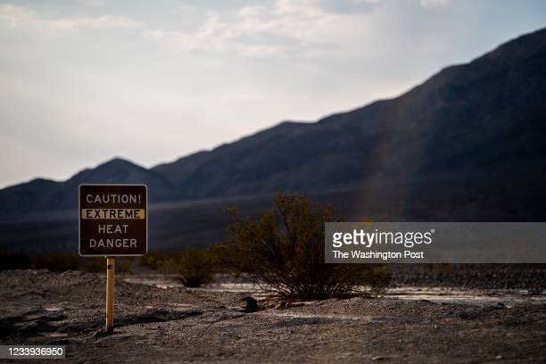 With the Amargosa Mountain Range in the background at sunrise, a sign warns park visitors of extreme heat danger along Highway 190 during a weekend...