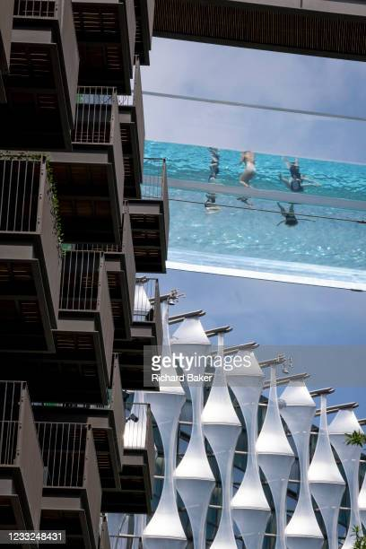 With the architecture of the US Embassy below, swimmers enjoy the waters of the Sky Pool, a 25 metres-long transparent water pool bridging two...