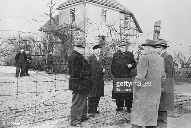 With the barbed wire barricade that symbolizes the Iron Curtain between them officials of the little town of Neustadt West Germany talk with...