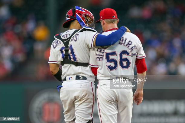 With the bases loaded Texas Rangers Catcher Robinson Chirinos visits the mound to talk with Pitcher Austin BibensDirkx during the game between the...