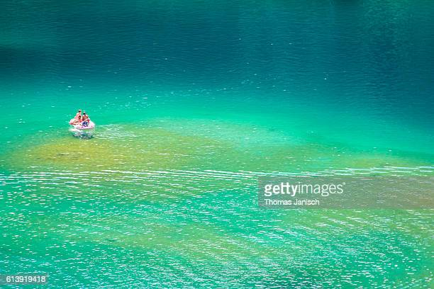 with the boat on lake caumasee, with it's different shades of green and blue water - エメラルドグリーン ストックフォトと画像