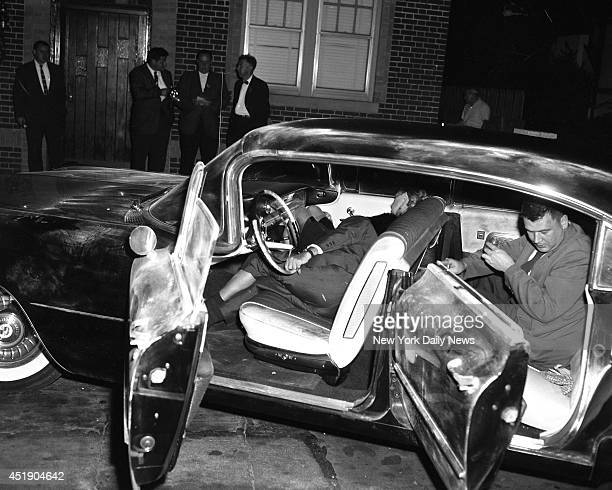 With the bodies of Little Augie Pisano and Janice Drake still slumped in death in the front seat detective takes fingerprints in back seat of death...