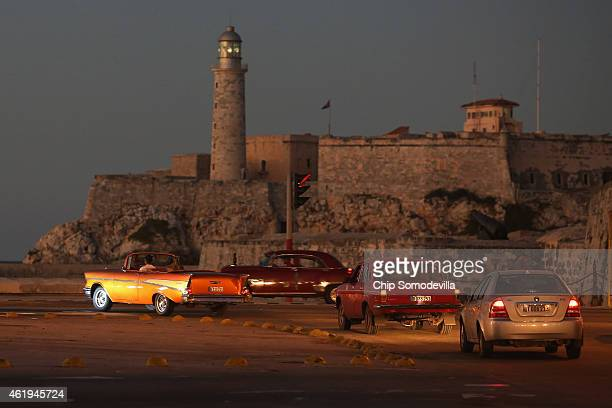 With the Castillo San Felipe del Morro standing in the background, old and new cars drive along the Paseo del Prado in the Habana Vieja neighborhood...
