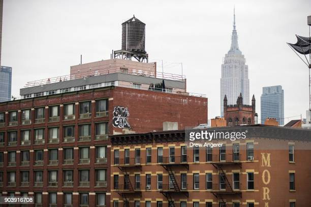 With the Empire State Building in the background apartment buildings stand in the Chelsea neighborhood in Manhattan January 11 2018 in New York City...