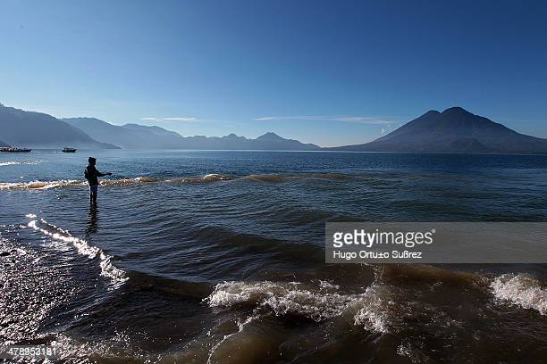 With the formation of volcanoes around Lake Atitlan, a child uses the quiet tide to fish. Panajachel in the Guatemalan highlands at 1,500 meters...