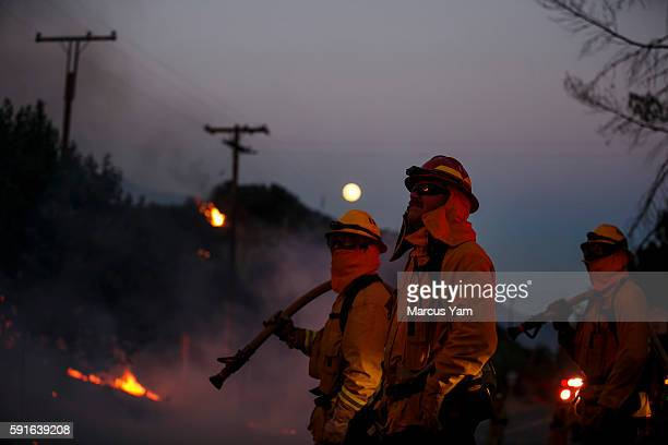 With the full moon in the background firefighters monitor the Blue Cut fire traveling on the side of Lytle Creek Road in San Bernardino County Calif...