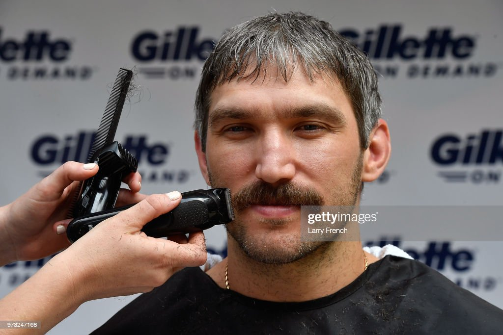 With the help of a barber, World Champion hockey star Alex Ovechkin gets his 'playoff beard' trimmed down with a clipper before completing his clean-shaven postseason look with a Gillette Fusion ProShield Razor on June 13, 2018 in Mclean, Virginia.