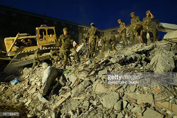 With the help of flood lights Algerian soldiers search for survivors under a collapsed building in the popular BordjelKiffan quarter of Algiers after...