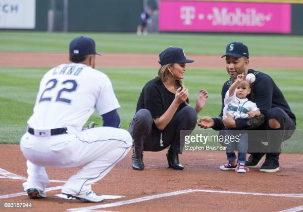With the help of mother Chrissy Teigen center and father John Legend Luna Stephens throws out the ceremonial first pitch to Robinson Cano of the...