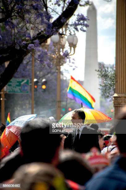 With the iconic Obelisco monument in the background a suited man stands among a crowd of LGBTQIA supporters Thousands of pride supporters marched...