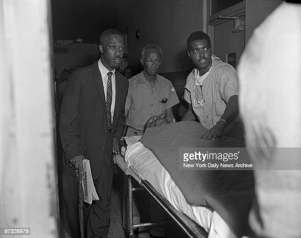 With the letter opener still protruding from his chest Dr Martin Luther King is wheeled into Harlem Hospital for treatment after being stabbed