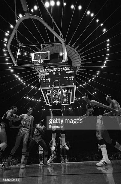 With the lights over the scoreboard forming a halo over the first NBA game played at The Forum San Diego Rockets' Tony Kimball picks off a rebound...
