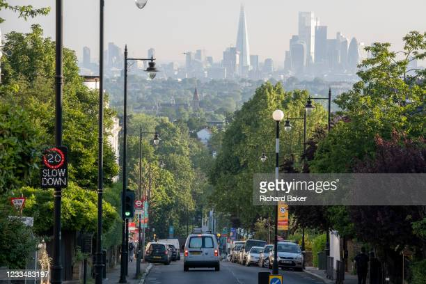 With the London skyline in the far distance, a white van descends the 20mph steep gradient of Gypsy Hill in Crystal Palace, on 16th June 2021, in...