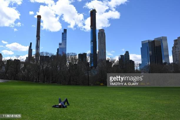 With the midtown skyline in the background a man takes in the sun at the Sheep Meadow in Central Park in New York City April 10 2019 The Sheep Meadow...