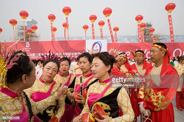 With the newly constructed National Aquatics Center in the background, a community dance group wait for their turn to perform in a celebration which...