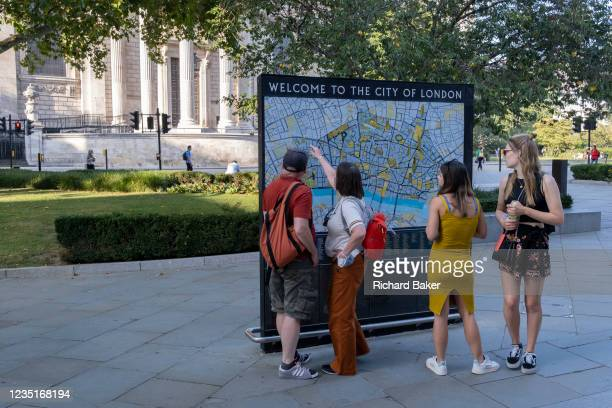 With the pillars and architecture of St Paul's Cathedral in the distance, visitors to London stop to view a detailed map of the City of London, the...