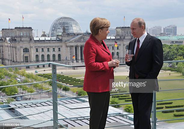 With the Reichstag building in the background Russia's President Vladimir Putin speaks with German Chancellor Angela Merkel on the roof of the...