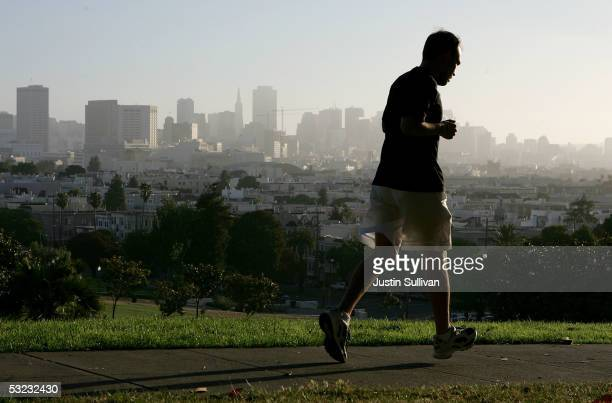 With the San Francisco skline in the background a jogger runs through Dolores Park July 13 2005 in San Francisco Runner's World Magazine has just...