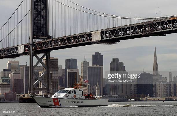 With the San Francisco skyline in the background a United States Coast Guard ship travels under the Oakland/San Francisco Bay Bridge on a routine...