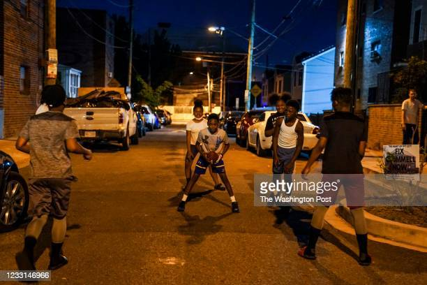 With the shuttered Crummell School looming in the background, kids - including Diamonte Powell C - play football in the street in front of their...