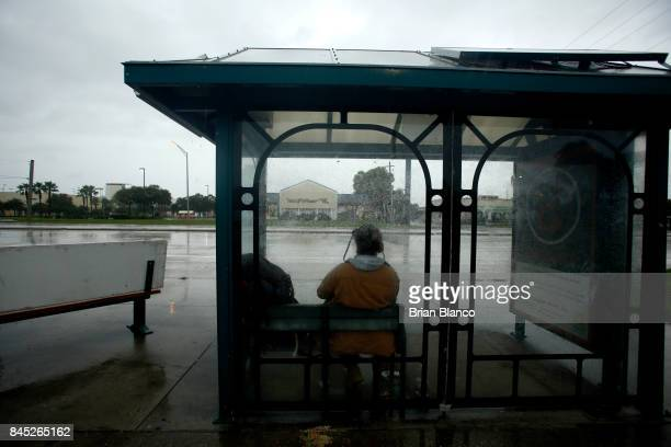 With the sky darkening and the wind picking up people hide from the rain at a bus stop ahead of Hurricane Irma on September 10 2017 in Tampa Florida...