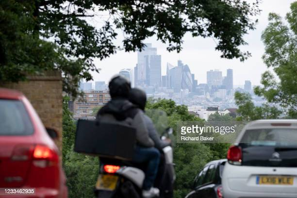 With the skyscrapers of the City of London, the capital's financial district, in the distance, motorists in morning rush-hour traffic, turn down...