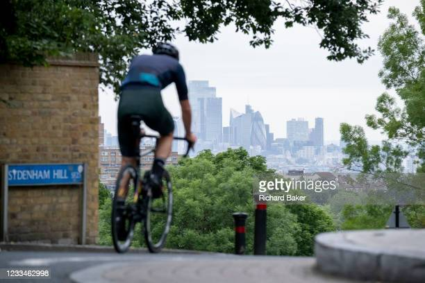 With the skyscrapers of the City of London, the capital's financial district, in the distance, a cyclist in morning rush-hour traffic, turnturns down...