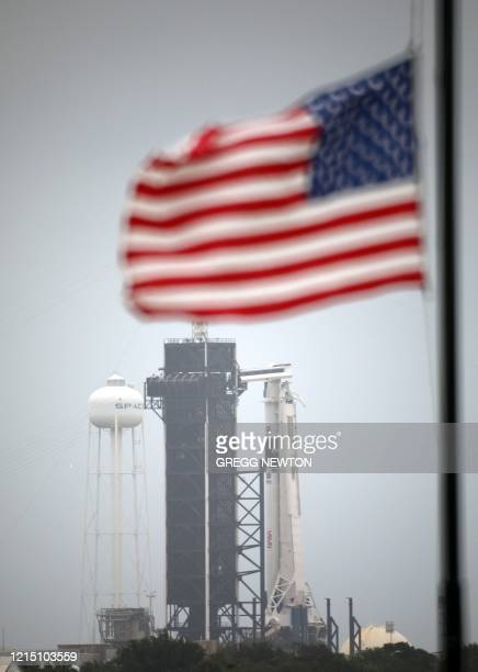 With the SpaceX Falcon 9 rocket at launch complex 39A looming in the distance a US flag flies at halfstaff on Memorial Day at the Kennedy Space...
