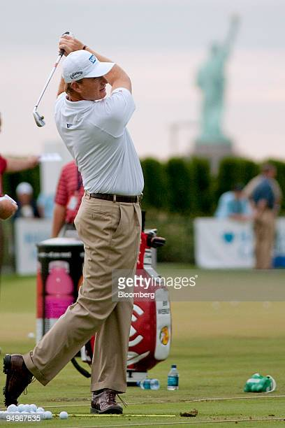 With the Statue of Liberty in the background golfer Ernie Els warms up on the driving range during The Barclays golf tournament at Liberty National...