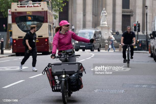 With the statue of Queen Anne and St Paul's Cathedral in the background, a woman delivery cyclist indicates and holds out her hand to make a left...