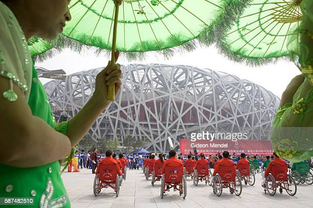 With the striking Beijing National Stadium looming in the background a group of disabled people in wheelchairs do a performance which was part of...