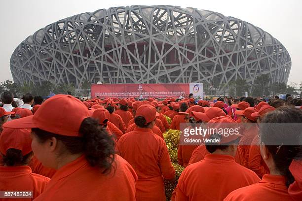 With the striking Beijing National Stadium looming in the background a community dance group performs during a celebration and marathon fun run which...