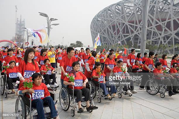 With the striking Beijing National Stadium looming in the background a group of disabled people in wheelchairs cermonially lead the start of a...
