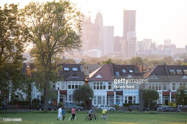 With the tall towers at Nine Elms in the distance, a sun sets below a line of homes and ash trees and a group of friends leave Ruskin Park after a...