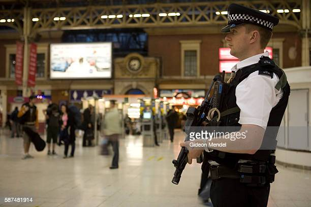 With the UK on a terror alert that has been raised to a critical level an armed policeman is part of a visible security presence at Victoria Station...