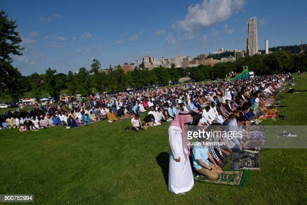 With the University of Pittsburgh's Cathedral of Learning seen in the background hundreds of Muslims gather in prayer to celebrate Eid alFitr which...