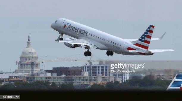 With the US Capitol dome in the distance an American Airlines airplane takes off from Ronald Reagan National Airport September 1 2017 in Washington...
