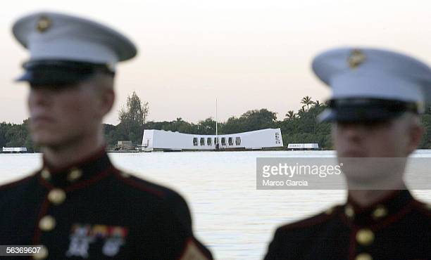 With the USS Arizona in the background, two US Marines stand at attention at the Pearl Harbor Memorial at dawn before the start of the ceremony...