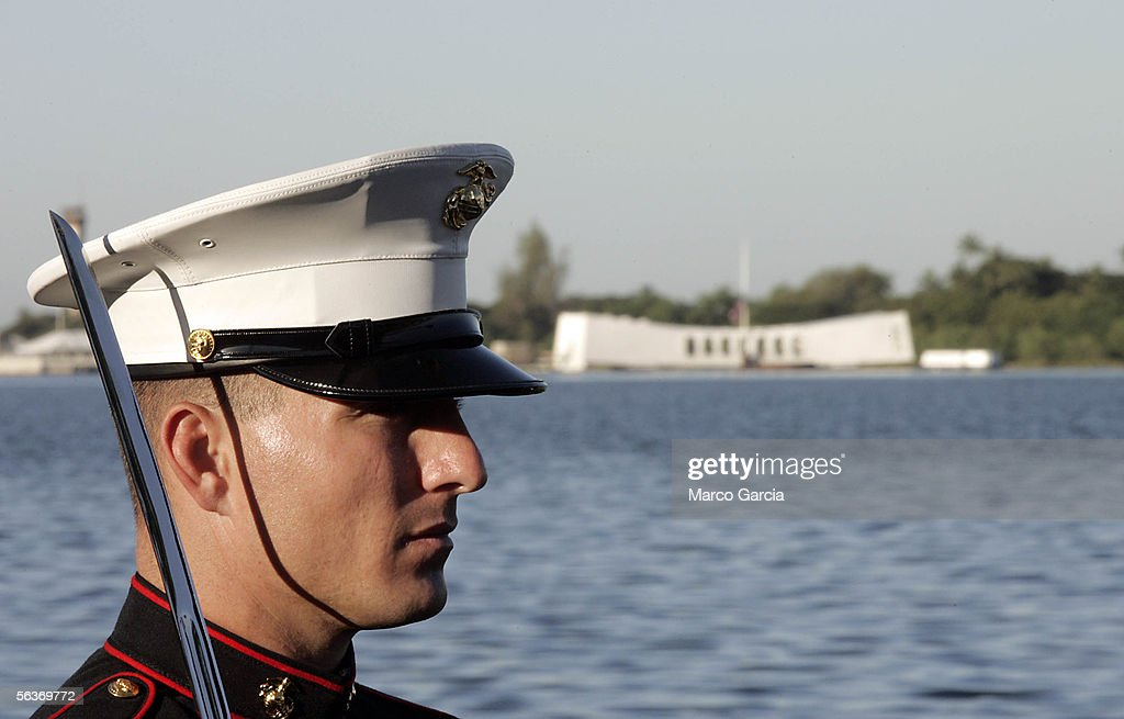 With the USS Arizona Memorial in the background, a U.S. Marine stands at attention during the ceremony honoring the 64th anniversary of the surprise attack on Pearl Harbor, December 7, 2005 at Pearl Harbor, Hawaii. Around the country, Pearl Harbor survivors and others paid tribute to those lost during the December 7, 1941 Japanese bombing of Pearl Harbor.