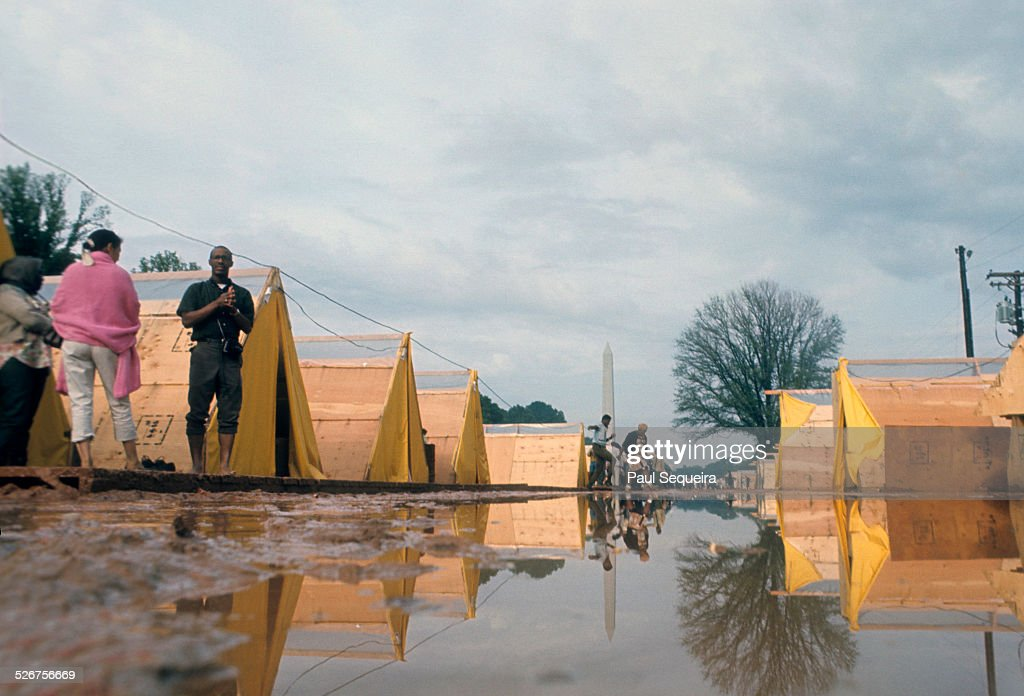 With the Washington Monument looming in the background, protesters stand outside their tents in a muddy field in Resurrection City, the shantytown that rose up as part of the Poor People's Campaign, on the Mall, Washington DC, May 1968.
