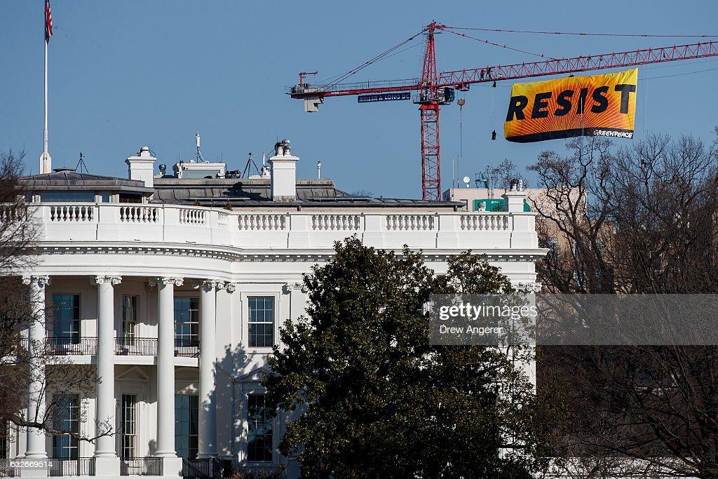 protesters climb atop a crane in washington d c の写真および