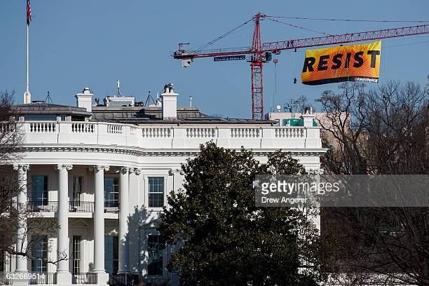 With the White House in the foreground protesters unfurl a banner atop a crane at the construction site of the former Washington Post office building...