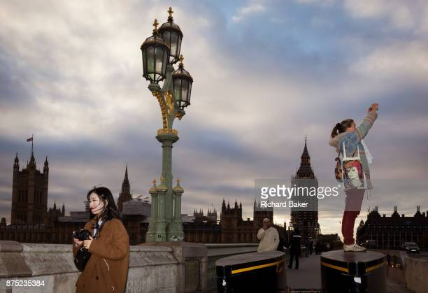 With the winter landscape of Westminster and the Houses of Parliament on the river Thames opposite tourists visit London including a woman with a...