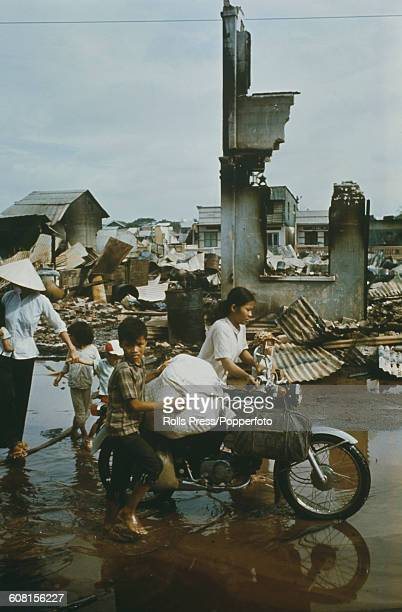 With their belongings packed on to a motorbike residents escape along a flooded street past a burnt out building in Saigon Vietnam during fighting...
