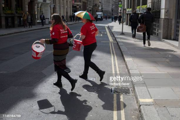With their donation buckets swinging two women charity fundraisers for the Red Cross cross Cornhill in the City of London the capital's financial...