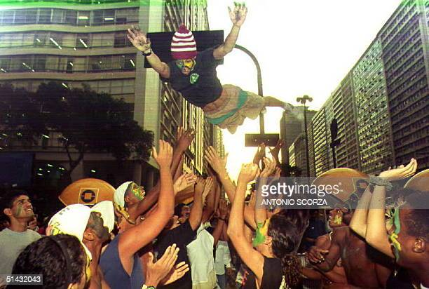 With their faces painted the same colors as the national flag students throw another student in the air 21 September 1992 in Rio de Janeiro Brazil...