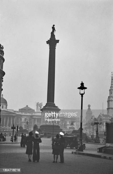 With their female companions, an American sailer and Marine view Nelson's Column and Trafalgar Square as part of a tour of landmarks in London,...